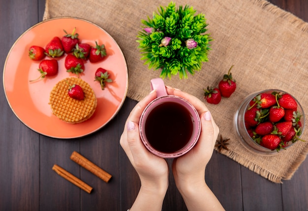 Top view of hand holding cup of tea and waffle biscuits with strawberries in plate and bowl and flower on sackcloth with cinnamon on wooden surface
