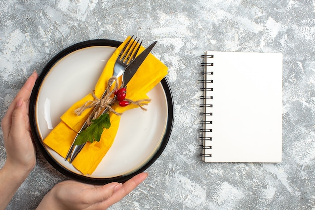 Top view of hand holding cutlery set for meal on a white plate and closed notebook on ice surface