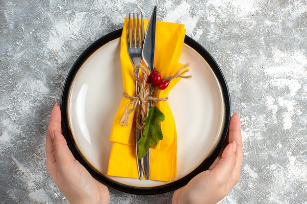 Top view of hand holding cutlery set for meal on a white plate on ice surface