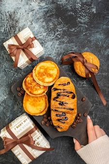 Top view of hand holding cutting board with tasty breakfast with pancakes croisasant stacked cookies beautiful gift boxes on dark surface