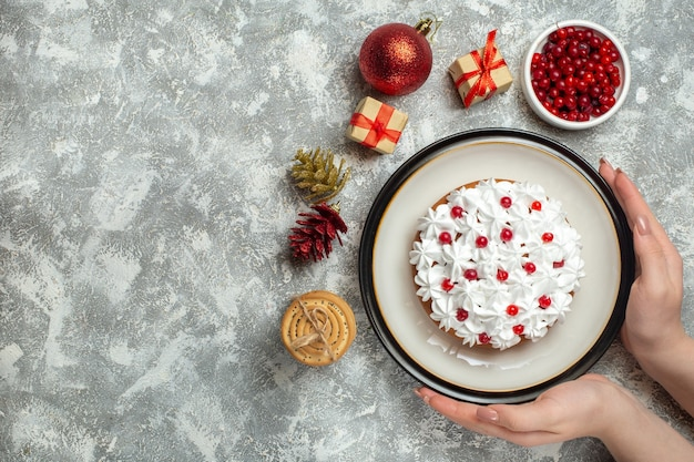 Top view of hand holding delicious cake with cream currant on a plate and gift boxes