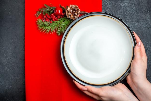 Vista superiore della mano che tiene piatti vuoti e rami di abete con cono di conifera accessorio decorazione su un tovagliolo rosso su sfondo scuro