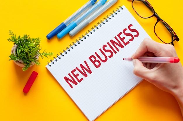 상위 뷰, 노란색 테이블에 노트북, 펜, 안경 및 녹색 꽃과 새로운 비즈니스 목록을 작성하는 연필을 들고 손. 새 해 복 많이 받으세요 개념의 비즈니스
