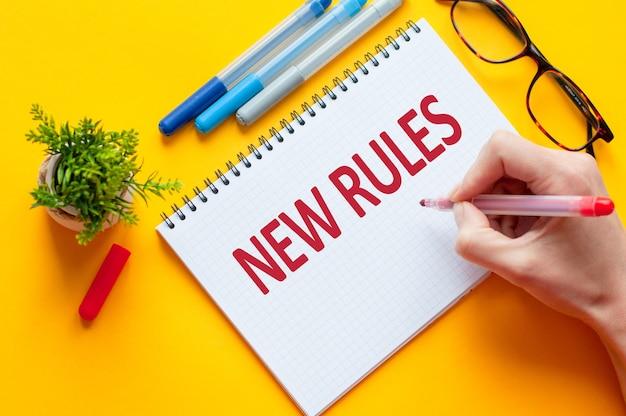 상위 뷰, 노란색 테이블에 노트북, 펜, 안경, 계산기 및 녹색 꽃과 함께 새로운 규칙 목록을 작성하는 연필을 들고 손. 비즈니스 및 교육 개념