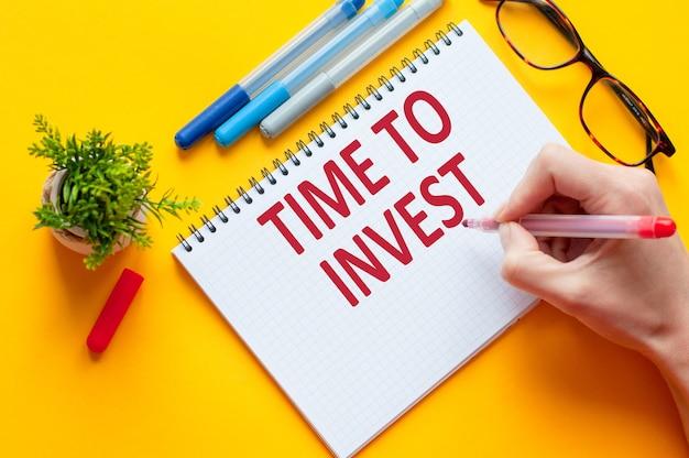 上面図、手持ちの鉛筆で書くtime to investリスト、ノート、ペン、メガネ、電卓、黄色いテーブルに緑の花。ビジネスと教育の概念