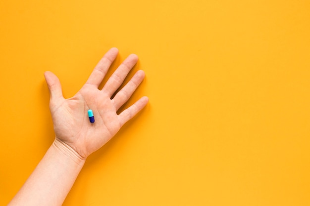 Top view hand holding a pill with copy space