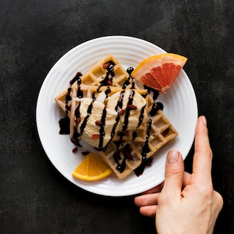Top view of hand holding plate with waffles covered in ice cream and chocolate sauce