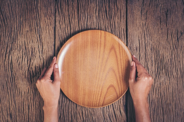 Top view hand holding plate on wood background