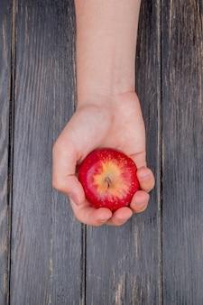 Vista superiore della mano che tiene mela rossa sulla tavola di legno
