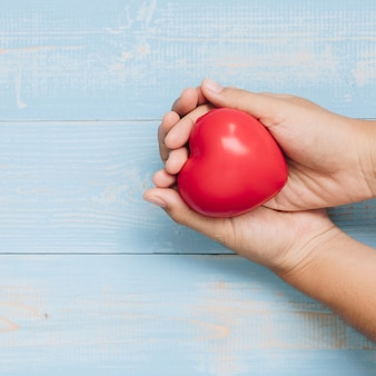 Top view hand holding red heart shape on blue pastel color wooden
