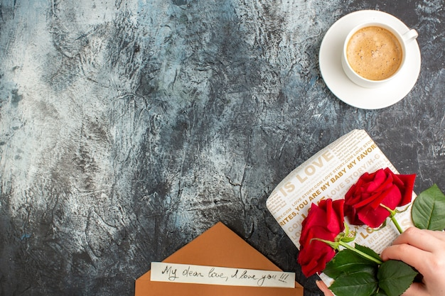 Top view of hand holding red roses on beautiful gift box and cup of coffee envelope with love letter on icy dark background