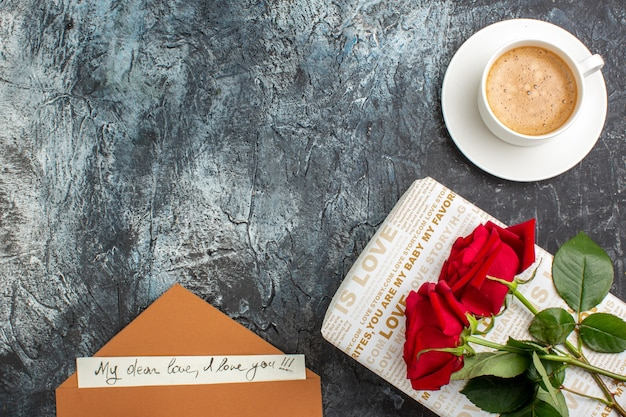 Vista dall'alto della mano che tiene le rose rosse su una bella confezione regalo e una busta di una tazza di caffè con lettera d'amore sul lato sinistro su sfondo scuro ghiacciato