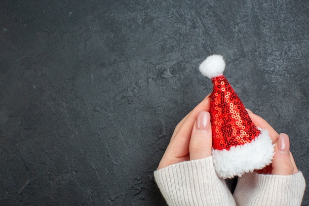 Top view of hand holding santa claus hat on the left side on dark background