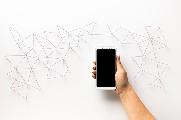 Vista dall'alto mano che tiene smartphone e rete di comunicazione internet