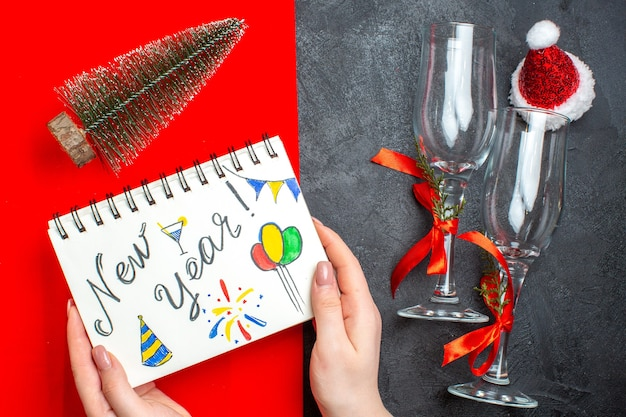 Top view of hand holding spiral notebook with new year drawing and christmas tree glass goblets on dark and red background