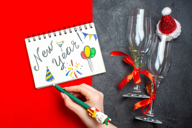 Top view of hand holding spiral notebook with new year writing and glass goblets santa claus hat on red and black background