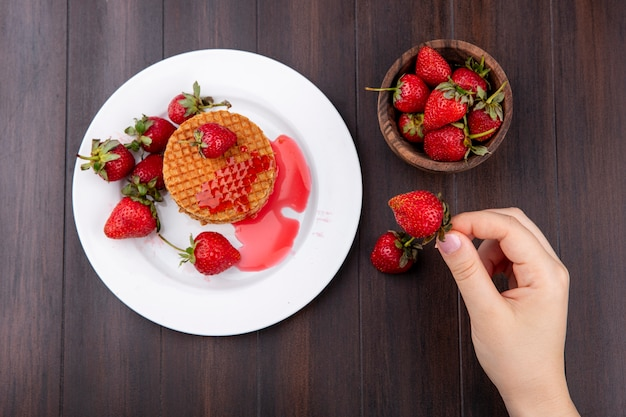 Top view of hand holding strawberry with waffle biscuits in plate and bowl of strawberry on wooden surface
