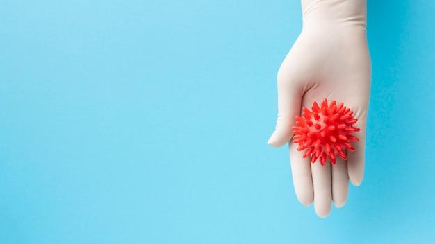 Vista dall'alto della mano che tiene il virus con lo spazio della copia