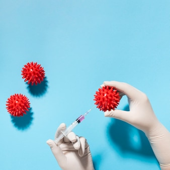 Top view of hand holding virus with syringe