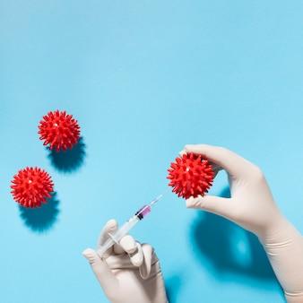 Vista dall'alto della mano che tiene il virus con la siringa