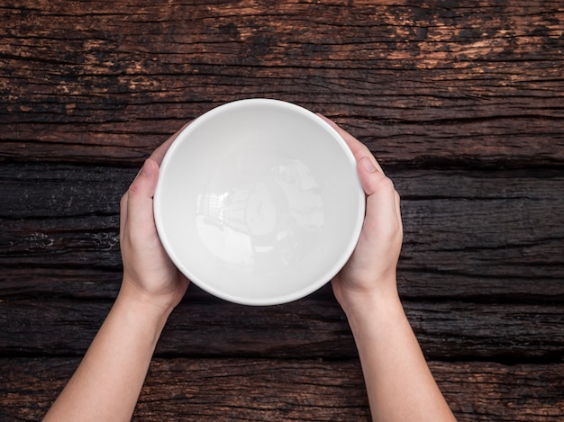 Top view hand holding white bowl