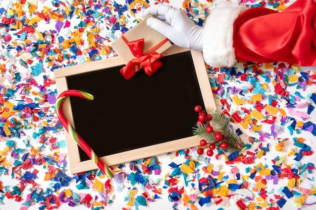 Вид сверху рука санта-клауса, держащего подарок