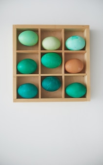Top view of hand-painted emerald easter eggs in wooden crate arranged in minimal composition on white background, copy space