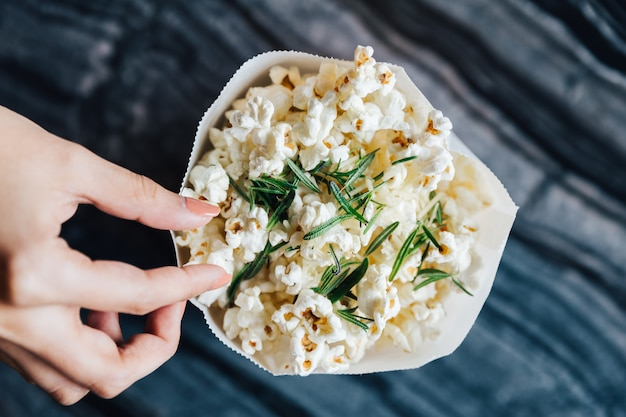 Top view of hand pinching a rosemary popcorn in paper bag on top marble table.