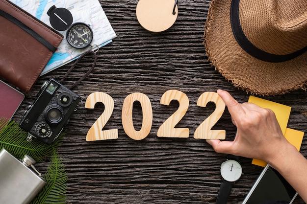 Рука вида сверху кладет номер с новым годом 2022 на деревянный стол с аксессуаром для приключений, планирование праздничных каникул.