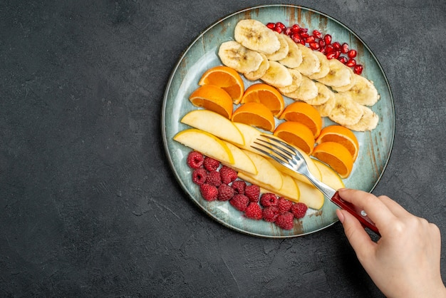 Top view of hand taking apple slices from collection of chopped fresh fruits on a blue plate on black table