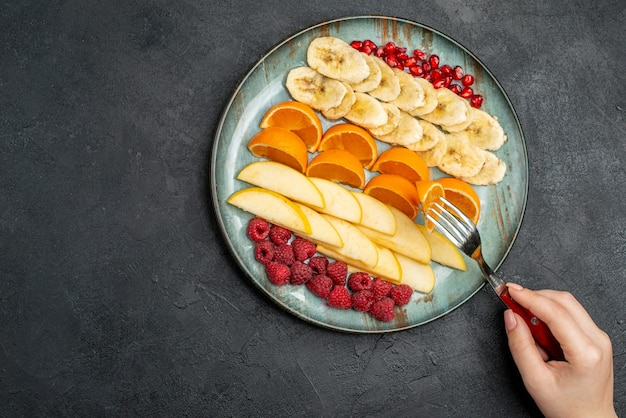 Top view of hand taking apple slices from with fork collection of chopped fresh fruits on a blue plate on black table