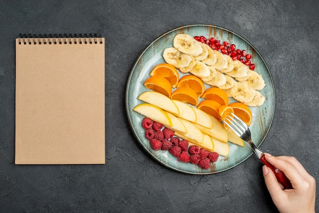 Top view of hand taking apple slices from with fork collection of chopped fresh fruits on a blue plate and spiral notebook on black table