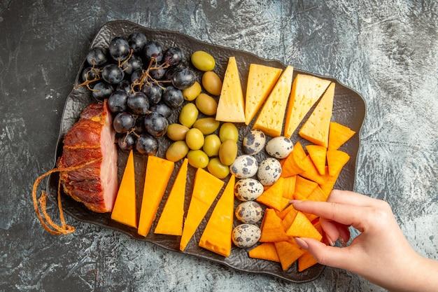 Vista dall'alto della mano che prende uno degli alimenti dal delizioso miglior spuntino per il vino su un vassoio marrone su sfondo di ghiaccio
