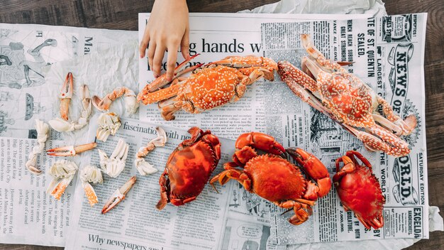 Top view of hand touching steamed flower crabs and giant mud crabs with separated parts of steamed crab