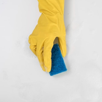 Top view of hand with cleaning glove holding sponge