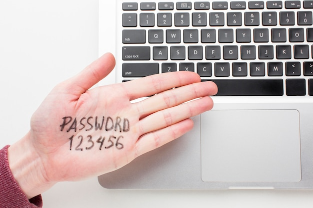 Top view of hand with password written on it and laptop