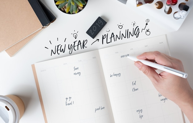 Top view of hand writing  new year's planning on open calendar planner