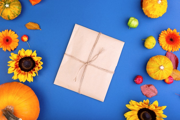 Top view of handcraft gift box with yellow and orange flowers and pumpkins on blue background. blank greeting card for creative work design. flat lay