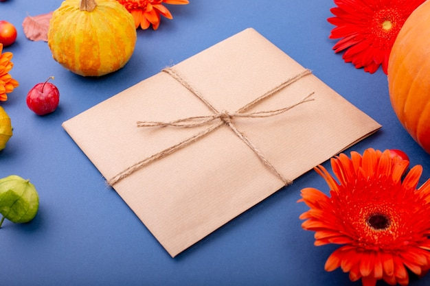 Top view of handcraft gift box with yellow and orange flowers and pumpkins on blue surface