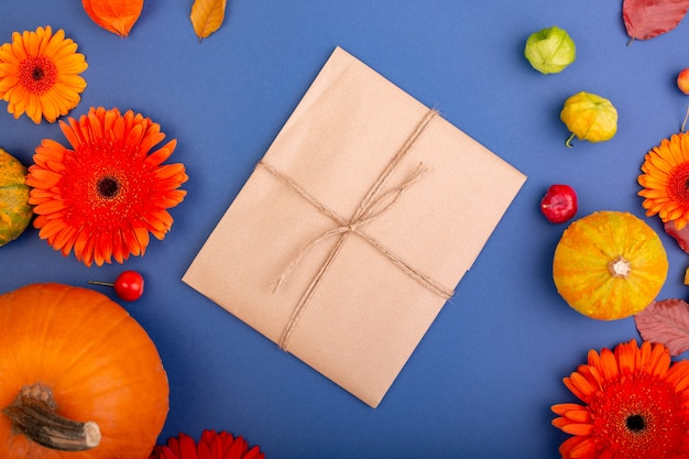 Top view of handcraft gift box with yellow and orange flowers and pumpkins on blue wall blank greeting card for creative work design. flat lay