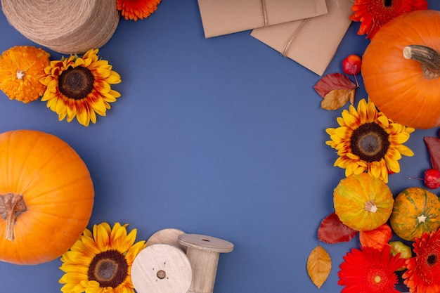 Top view of handcraft gift box with yellow and orange flowers, rope reel and pumpkins on blue background