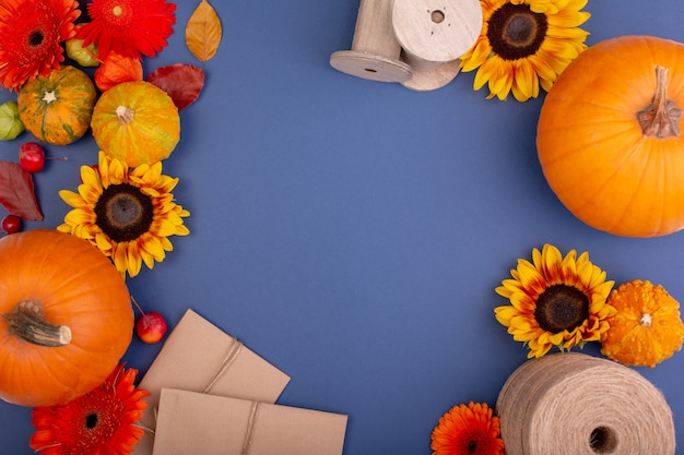 Top view of handcraft gift box with yellow and orange flowers, rope reel and pumpkins on blue wall blank greeting card for creative work design. flat lay