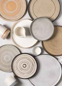 Top view of handmade ceramics, empty craft ceramic plates and cups on light background.