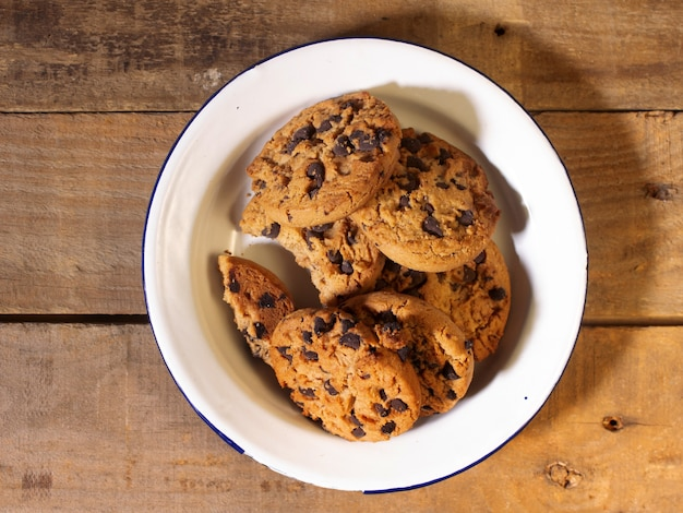 Top view of handmade chocolate chip cookies on a rustic wood background
