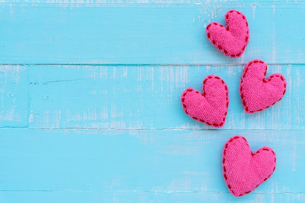 Top view of handmade pink heart on blue and white color wooden background