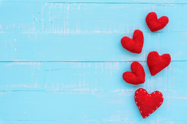 Top view  of handmade red heart on blue and white color wooden background