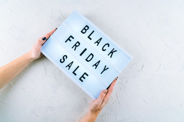 Top view of hands, black friday promotion sale words on lightbox holded by human hands. flat lay