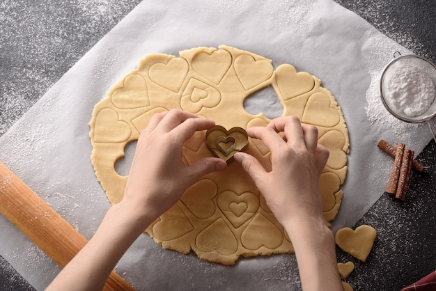 Top view hands cut out hearts from cookie dough on kitchen gray table, cinnamon sticks, rolling pin and powdered sugar