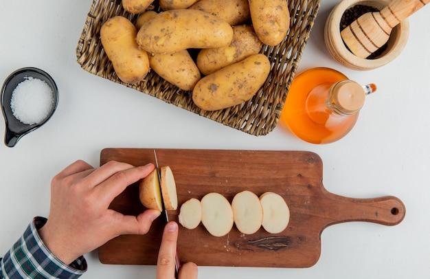 Vista superiore delle mani che tagliano patata con il coltello sul tagliere e altri in pepe nero del sale del burro del piatto su superficie bianca
