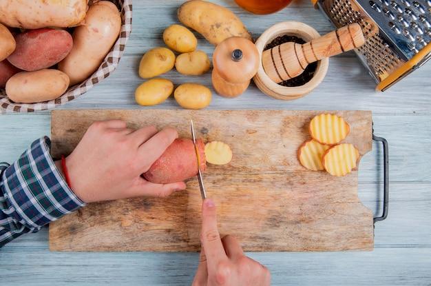 Vista superiore delle mani che tagliano patata con il coltello sul tagliere con altri quelli in cestino con la grattugia dei semi del pepe nero e altre patate su superficie di legno